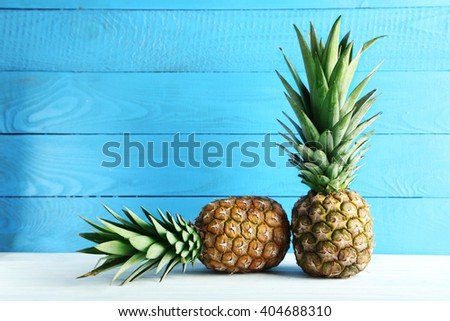 Ripe pineapples on a white wooden table #404688310