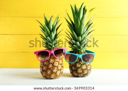 Ripe pineapples with sunglasses on a white wooden table