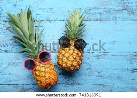 Ripe pineapples with sunglasses on blue wooden table #741816091