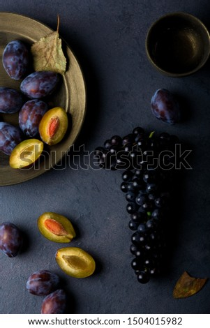 Ripe plums and ripe black grapes on the table. Dark background. Flat lay. Top view.