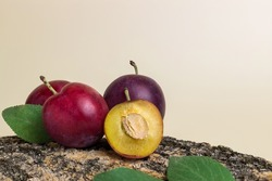 Ripe plums with leaves. Half with bone. Harvest fruit from the garden.