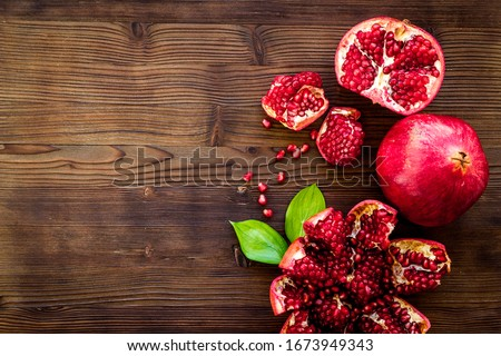 Ripe pomegranate fruit near leaf on dark wooden background top-down copy space Сток-фото ©