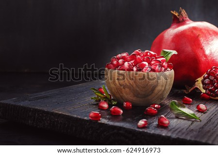 Ripe pomegranate fruit on a old  black wooden vintage background.