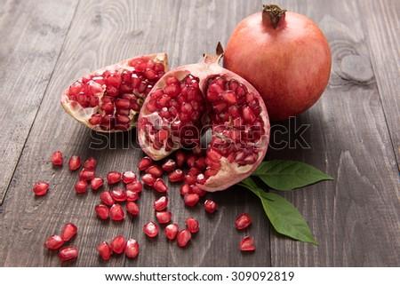 Ripe pomegranate fruit on wooden vintage table.
