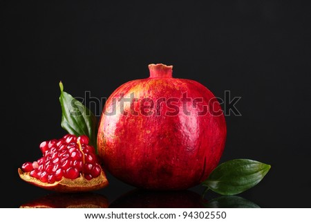 ripe pomegranate fruit with leaves on black background