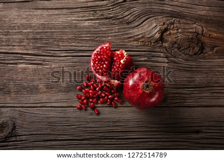 Ripe pomegranate fruits on the wooden background. Top view with copy space.