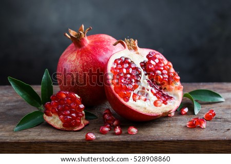 Shutterstock ripe pomegranate with leaves on a wooden board on a dark background