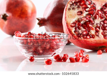 Ripe pomegranates and glass bowl of seeds on white background