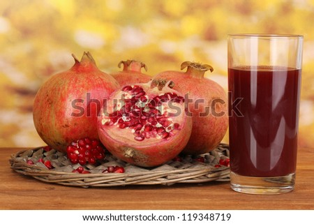 Ripe pomegranates on wicker cradle with glass of pomegranate juice on wooden table on autum background