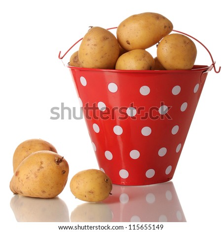 Ripe potatoes in red pail isolated on white