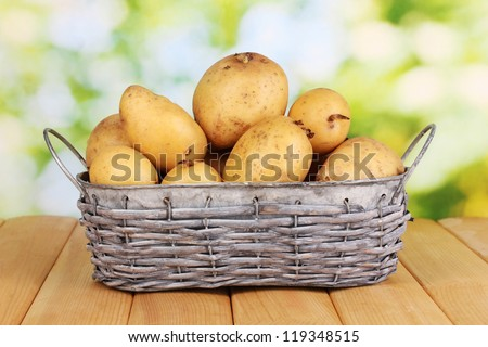 Ripe potatoes on basket on wooden table on natural background