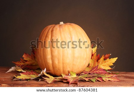 ripe pumpkin and autumn leaves on wooden table on brown background
