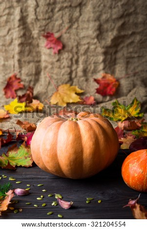 Ripe pumpkins and autumn leaves on wooden background #321204554
