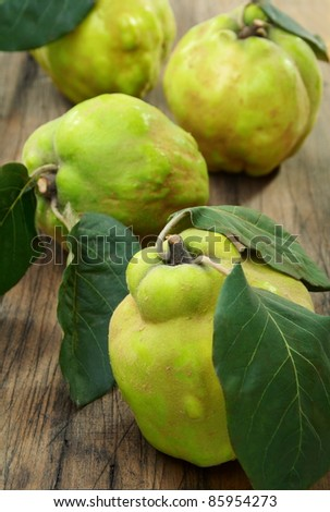Ripe quince is on an old wooden table.