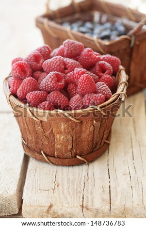 Ripe raspberries and blueberries in a basket