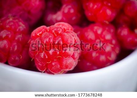 Ripe raspberries in a white dish close up