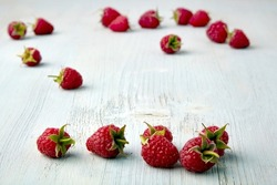 Ripe raspberries with cuttings are scattered at random on a light blue wooden table