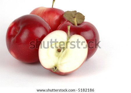 Ripe red apple cut in half in front of whole apples.