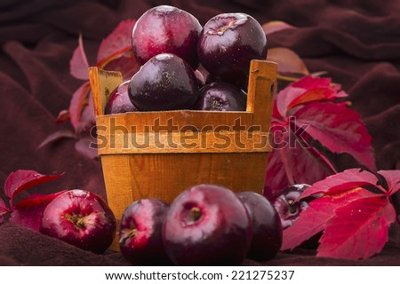 Ripe red apple red tubs wild grape leaves, ornamental background