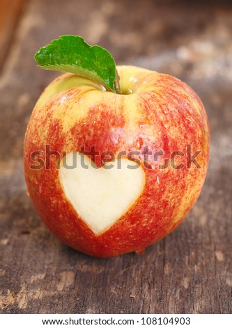 Ripe red apple with a heart shape neatly cut of the skin on a textured weathered wooden surface
