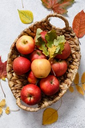 Ripe red apples in wooden basket and autumn dried leaves on bright light background. Autumn flat lay, top view