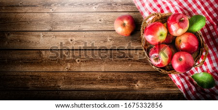 Ripe red apples in wooden box top view on rustic table. Wide apple banner with space for your text