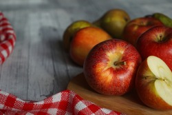 Ripe red apples on wooden table. Green pears in background, checked red & white tablecloth in foreground and on left side. One apple is cut in half. Copy space.