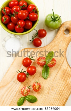 Ripe red cherry tomatoes are accented with basil and sprinkled with kosher salt.