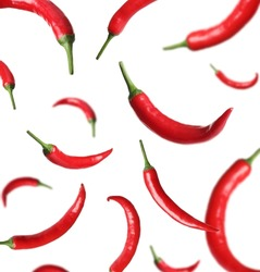 Ripe red chili peppers falling on white background