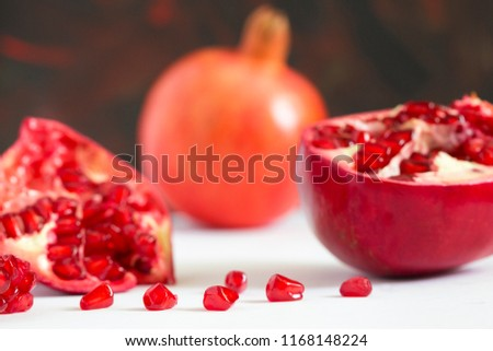 Ripe red fruit pomegranate with seeds on white background. close-up photo shallow depth of field #1168148224