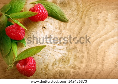 Ripe red raspberries and leaves on a patterned woodgrain texture with copyspace