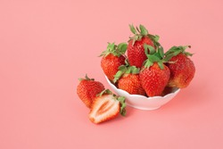 ripe red strawberries in a bowl on pink background. Heap of fresh strawberries in bowl. Fresh ripe delicious strawberries in a white bowl on pink background
