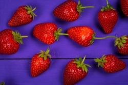 Ripe red strawberries on a purple wooden background