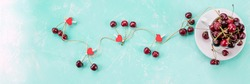 Ripe red sweet cherries with red heart on grungy table. Romantic love concept.Fresh red berries,chery,harvest concept, vitamins food. prevention of cardiovascular diseases. web banner.copy space