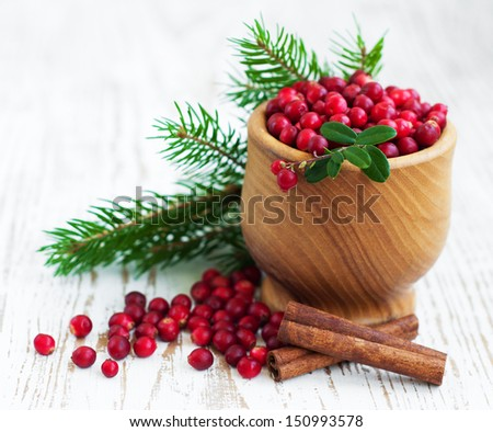 Ripe red wild cranberries on a wooden background