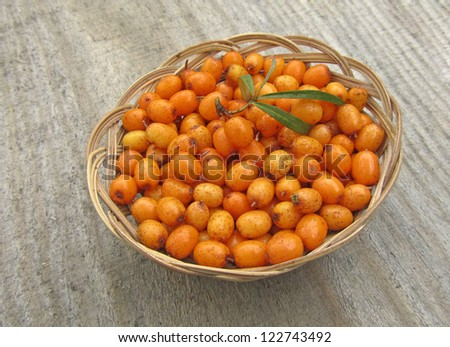 ripe sea buckthorn in basket on wooden background, close-up