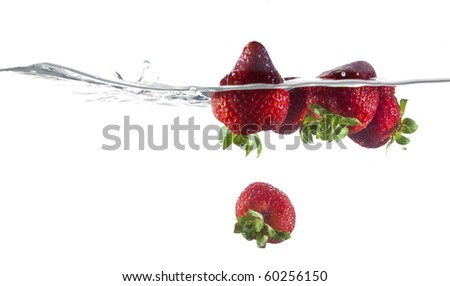 Ripe Strawberries Floating In Water - stock photo