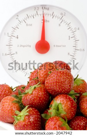 Ripe Strawberry's with Weight Scales shot against a plain background.