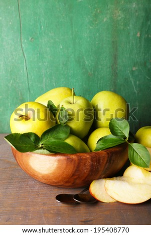 Ripe sweet apples with leaves in bowl on wooden background