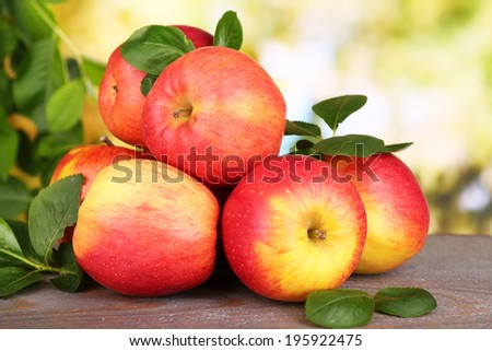 Ripe sweet apples with leaves on nature background