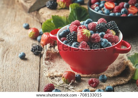 Ripe sweet different berries in red bowl on rustic wooden table. Harvest Concept #708133015