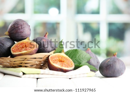 Ripe sweet figs with leaves in basket, on wooden table, on window background