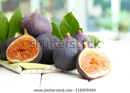 Ripe sweet figs with leaves, on wooden table, on window background