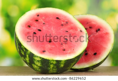Ripe sweet watermelon on wooden table on green  background
