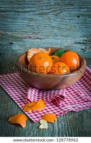 Ripe tangerines in a bowl on a wooden background