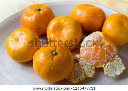 ripe tangerines on a plate, peeled tangerine, tangerine skin #1265479711