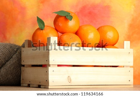 Ripe tasty tangerines with leaves in wooden box on table on orange background