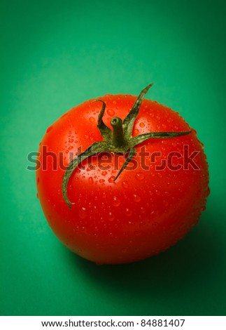 Ripe tomato on green background