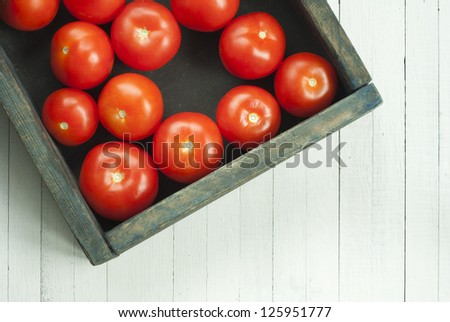 ripe tomatoes in rustic wooden box, on white wood table
