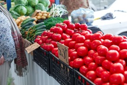 Ripe tomatoes on the counter of the Belarussian market. Fresh vegetables in the street bazaar. Small tomatoes.